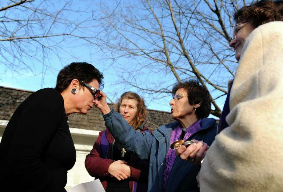"The Rev. Louise Kalemkerian, of Christ Episcopal Church Tashua, administers ashes to Nancy Masso, of Brookfield, on Ash Wednesday, Feb. 22, 2012 during ìAshes to Go,î a joint effort between Grace Church, Christ Church and Trinity Episcopal Church.  Masso, a teacher in Monroe, was looking for a service to fit her schedule when she read about the ""Ashes to Go"" event which was the perfect fit.  The Rev. Elsa Worth, center left, of Grace Episcopal Church, and The Rev. Ellen Kennedy, far right, of Trinity Episcopal Church, look on. Photo: Autumn Driscoll / Connecticut Post"