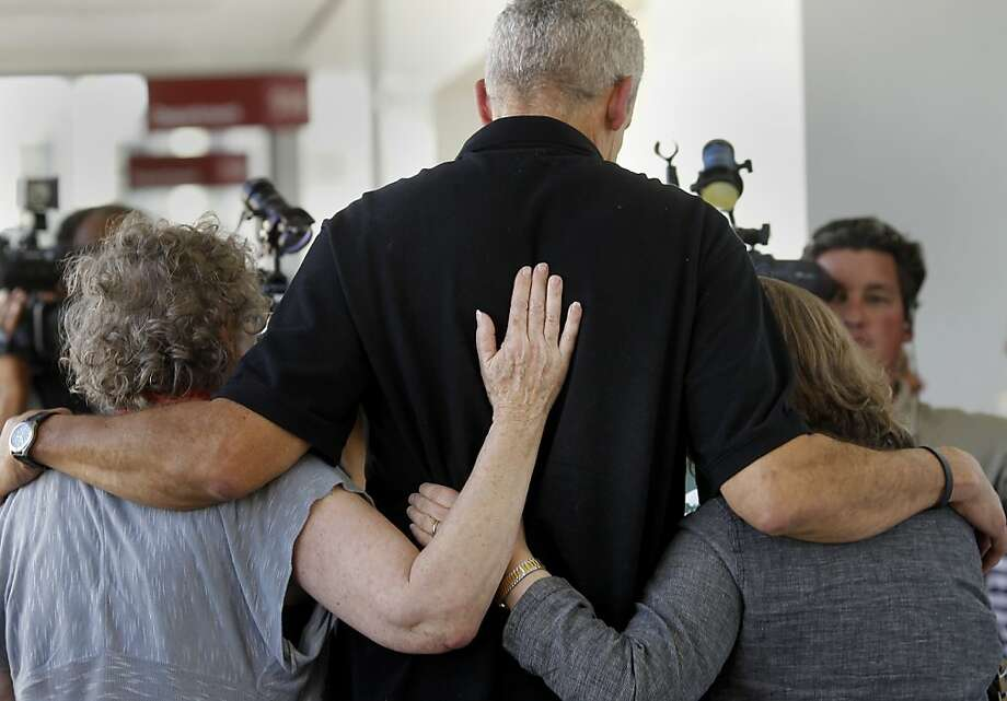 Al DeWitt, Daniel's father, (center) is comforted by relatives and friends as he walks past the media. Berkeley hills slaying suspect Daniel Jordan DeWitt was arraigned Wednesday February 22, 2012 for the bludgeoning of Peter Cukor in an Oakland, Calif. courtroom. Photo: Brant Ward, The Chronicle