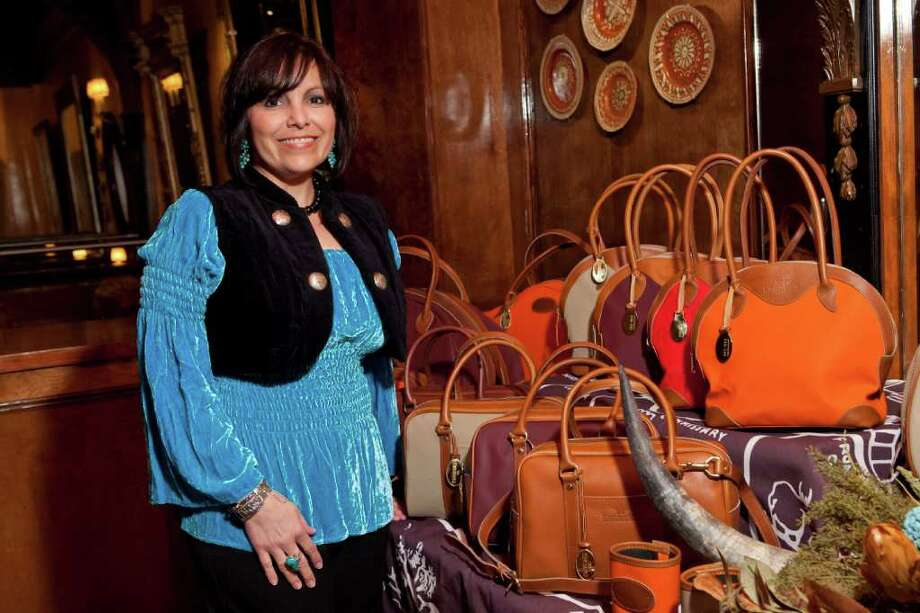 Rose Morales, general manager of King Ranch Saddle Shop, shows off the handbag collection with new colors, like orange. Photo: Bruce Bennett / Houston Chronicle
