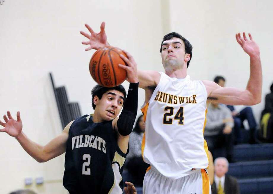 At left, Tyler Fernandez # 2 of Rye Country Day School goes for a rebound against Billy Murphy # 24 of Brunswick School during the FAA boys quarterfinal basketball playoff game between Brunswick School and Rye Country Day School at Rye Country Day School in Rye, N.Y., Wednesday, Feb. 22, 2012. Photo: Bob Luckey / Greenwich Time