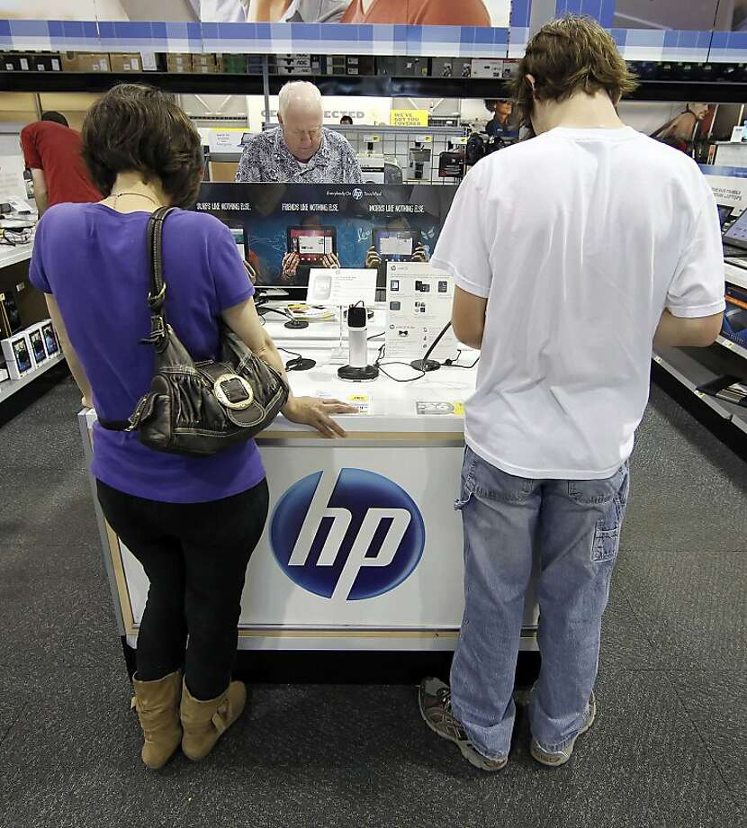 Shopper Sean Eastland, right, and his mother Erin Eastland look at a Hewlett-Packard Co. TouchPad tablet computer at a Best Buy Co. store in Orem, Utah, U.S., on Wednesday, Aug. 17, 2011. Best Buy Co. has sold less than 10% of 270,000 TouchPads in its inventory, AllThingsD's Arik Hesseldahl said earlier, citing a source who has seen internal HP reports. Photographer: George Frey/Bloomberg *** Local Caption *** Sean Eastland; Erin Eastland Photo: George Frey, Bloomberg