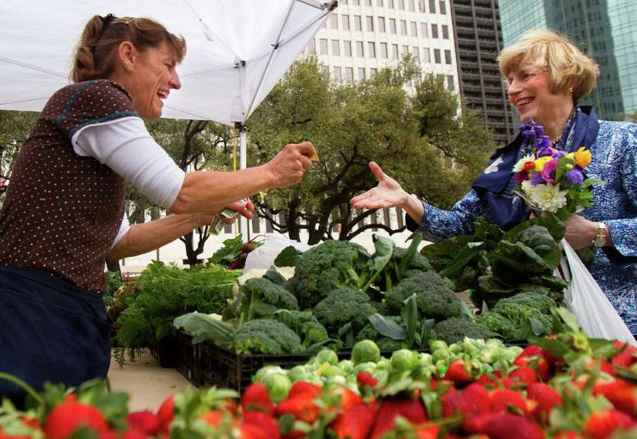 Theresa Atkinson, left, returns change to Fran Steele, right, after she purchased produce at the Farmer's Market outside City Hall Wednesday, Feb. 22, 2012, in Houston. Wednesday kicked off the Spring Season for the market with more than 35 vendors. Photo: Cody Duty, Houston Chronicle / © 2011 Houston Chronicle