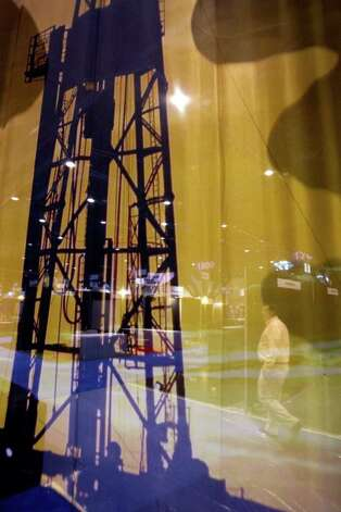 A man walks past an image of an oil derrick for one of the exhibitors during set up at the North American Prospect Expo at the George R. Brown Convention Center Wednesday, Feb. 22, 2012, in Houston. The conference offers a marketplace for trading oil and gas properties and forums for tracking trends in the oil and gas industry. Photo: Brett Coomer, Houston Chronicle / © 2012 Houston Chronicle