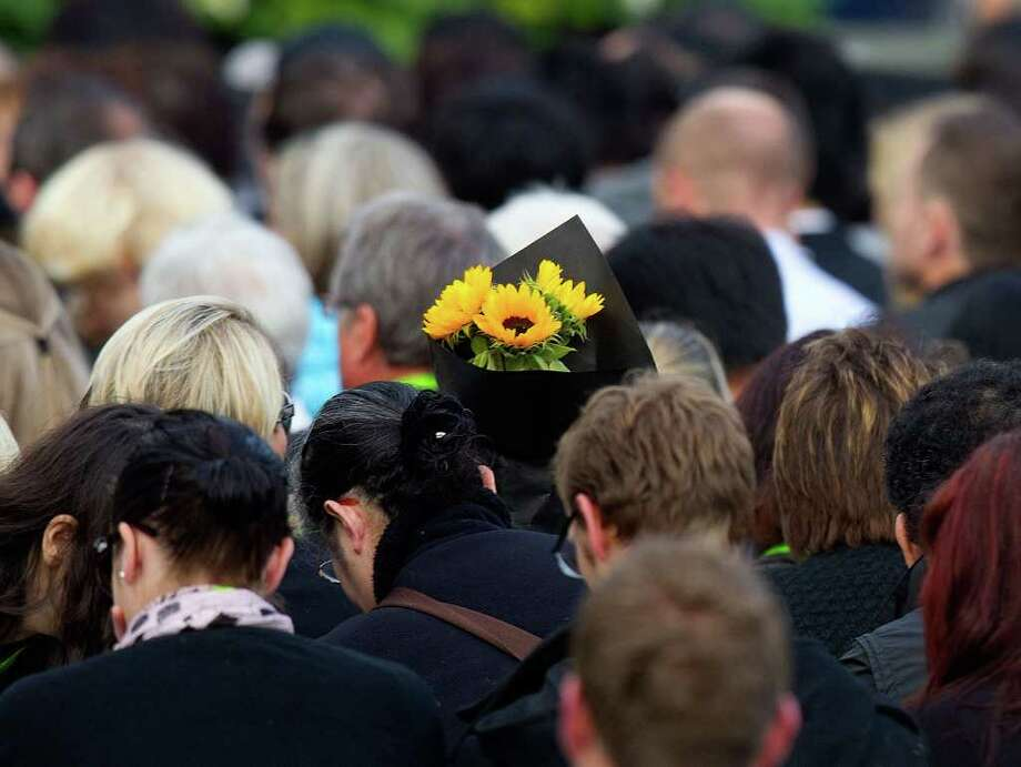 Families bring flowers to lay at the building site were their loved ones were lost during the February 22nd quake at the remembrance service in Latimer Square in Christchurch on February 22, 2012  one year after a 6.3 quake hit New Zealand's second largest city, killing 185 people, flattening office blocks, buckling roads and bringing historic buildings crashing down. Photo: MARTY MELVILLE, AFP/Getty Images / AFP