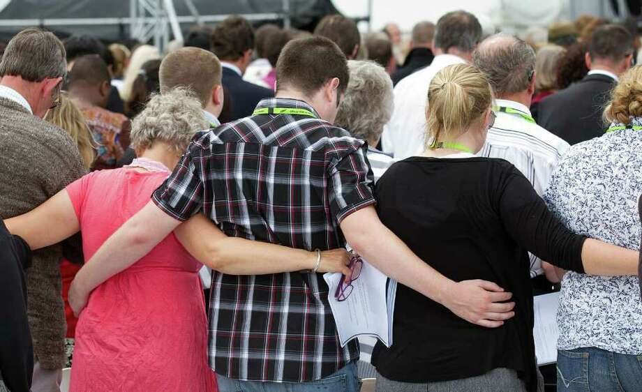 Families who lost loved ones hold each other during a remembrance service in Hagley Park in Christchurch on February 22, 2012, one year after a 6.3 quake hit New Zealand's second largest city. Photo: MARTY MELVILLE, AFP/Getty Images / AFP