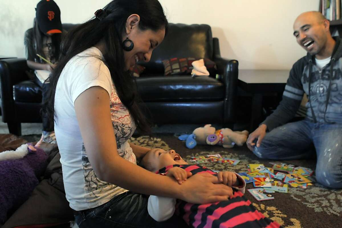Oscar Luna, right, and his wife, Lucia, play with their year-old daughter, Sofia in their San Pablo, Calif., home on Sunday, February 19, 2012, as their daughter, Isabel, 8, does her homework. Luna is a delivery driver for BiRite Foodservice Distributors. He moved out of the city to San Pablo about a year ago after he and his wife had their second child and they couldn't afford a larger place in San Francisco.