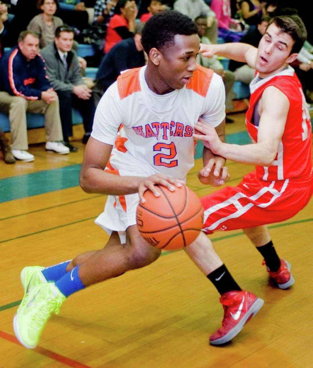 Danbury High School's Danjoel Harris works the ball around Greenwich High School's Alejandro Rodriguez during a game at Danbury. Wednesday, Feb. 22, 2012