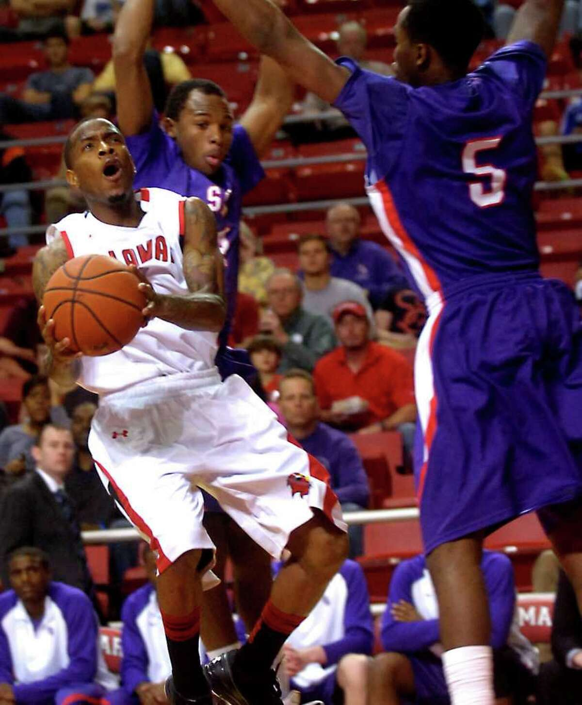 Lamar's Anthony Miles looks to shoot while a under pressure from Stephen F. Austin's Darius Gardner and Hal Bateman at Lamar University in Beaumont, Wednesday, February 22, 2012. Tammy McKinley/The Enterprise