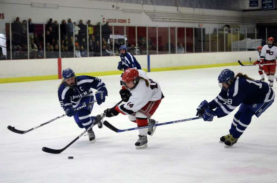 New Canaan's Madzie Carroll (14) splits Darien defenders Emily Tropsa (16) and Galen Rohn (18) on her way to the goal during the girls ice hockey game at Darien Ice Rink on Wednesday, Feb. 22, 2012. Photo: Amy Mortensen