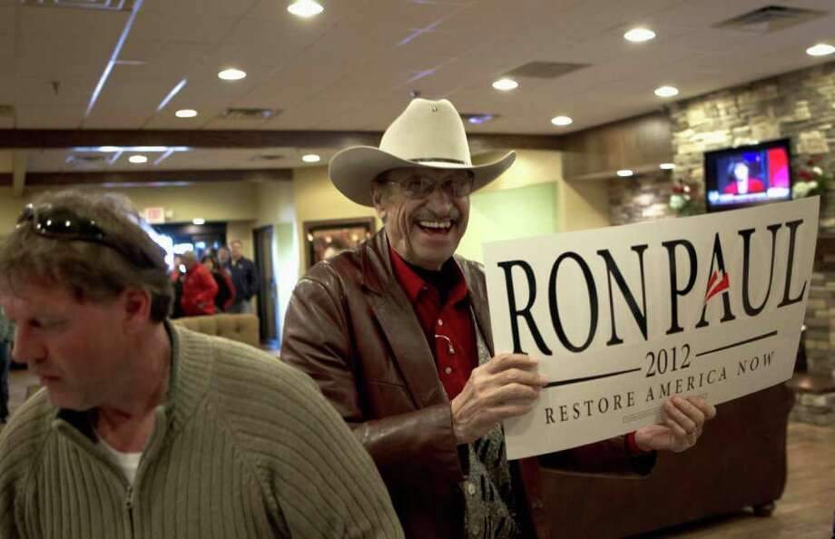 Bill Haverluk laughs after getting a poster of Republican presidential candidate Rep. Ron Paul, R-Texas, prior to a town hall meeting in Dickinson, N.D., Sunday, Feb. 19, 2012, ahead of North Dakota's Republican statewide presidential caucus which is scheduled for March 6. Photo: Nati Harnik, Associated Press