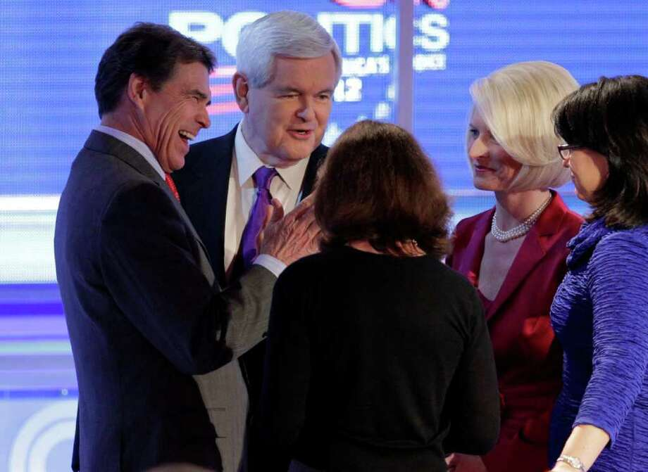 Texas Gov. Rick Perry, left, joins Republican presidential candidate former House Speaker Newt Gingrich, center, and wife Callista, second from right, following a Republican presidential debate Wednesday, Feb. 22, 2012, in Mesa, Ariz. Photo: Jae C. Hong, Associated Press / AP