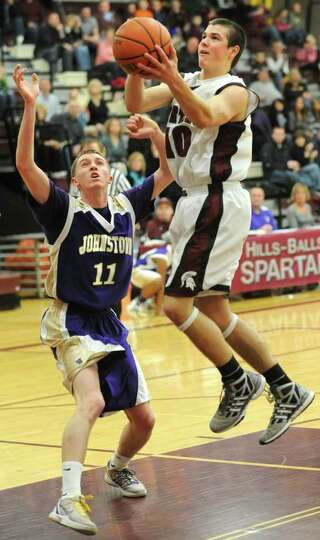 Robert Knightes of Burnt Hills drives to the basket against Cameron Husain of Johnstown during a bas
