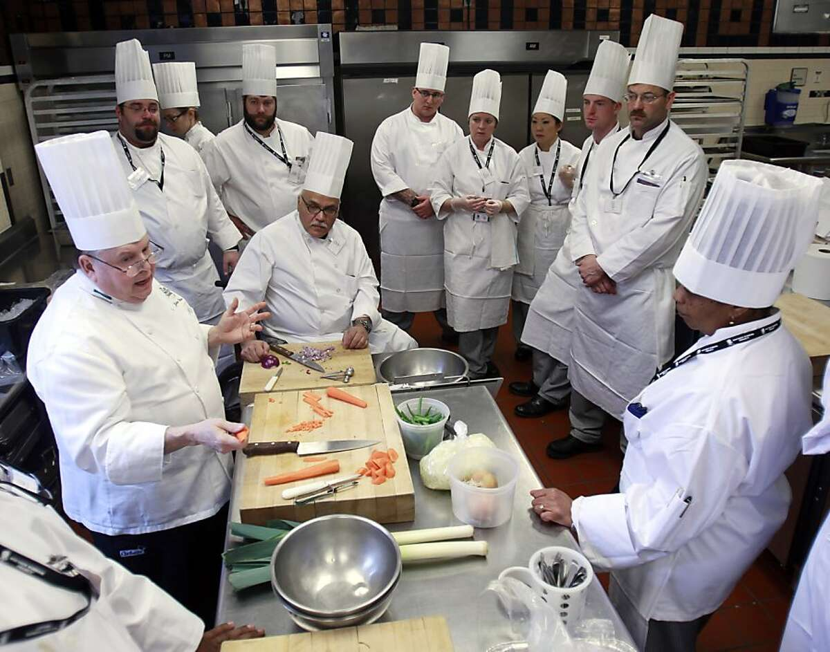 Chef John DeShetler, left, speaks to members of the Wounded Warrior Project taking part in a culinary bootcamp at the Culinary Institute of America in Hyde Park, N.Y., on Wednesday, Feb. 15, 2012. (AP Photo/Mike Groll)