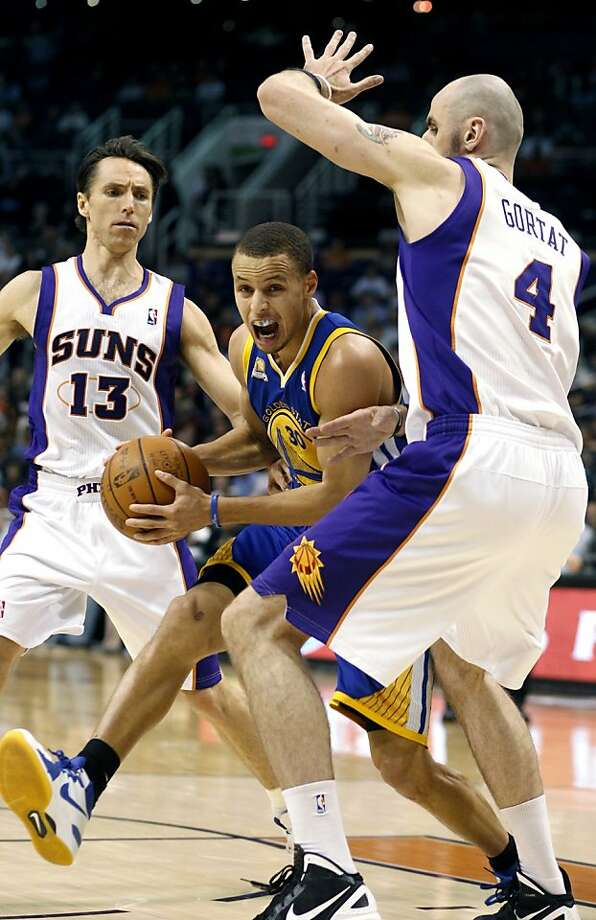 Golden State Warriors guard Stephen Curry, center, drives to the basket between Phoenix Suns guard Steve Nash, left, and center Marcin Gortat, right, of Poland, in the first quarter of an NBA basketball game Wednesday, Feb. 22, 2012, in Phoenix. Photo: Paul Connors, Associated Press