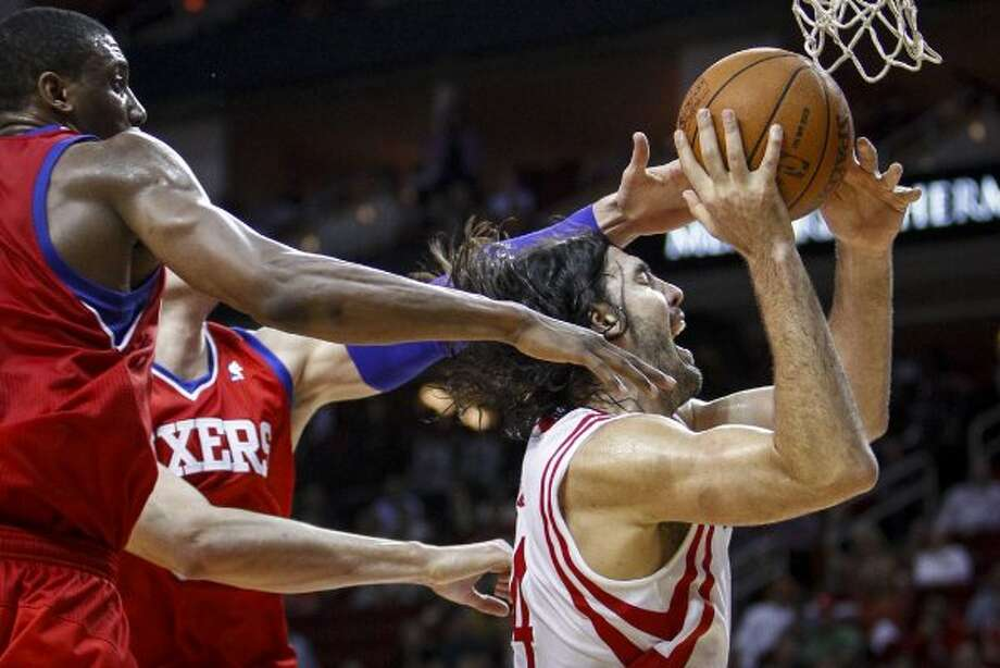 Houston Rockets power forward Luis Scola (4) drives to the basket as Philadelphia 76ers forward Thaddeus Young (21) and Philadelphia 76ers center Nikola Vucevic (8) defend during the second half. (Michael Paulsen / Houston Chronicle)