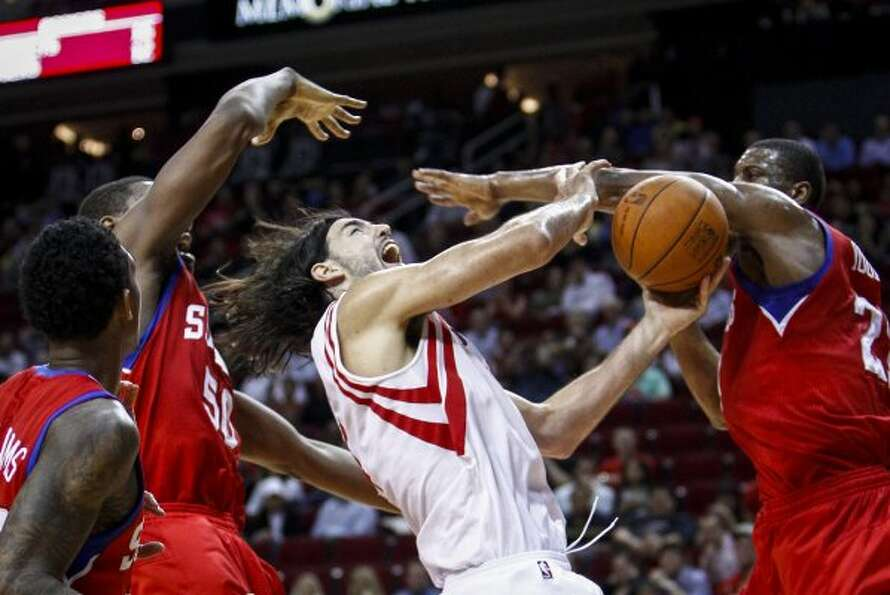 Houston Rockets power forward Luis Scola (4) loses the ball as he is swarmed by Philadelphia 76ers p