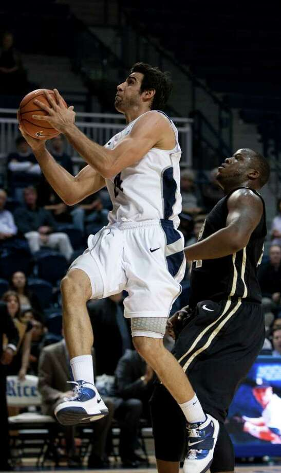 Rice Owls forward Arsalan Kazemi, left, takes a shot during the second half of the NCAA basketball game between the Rice Owls and the UCF Knights at Tudor Fieldhouse on Wednesday, Feb. 22, 2012, in Houston.  Rice defeated UCF 83-74 as Owls head coach Ben Braun recorded his 600th career win. Photo: Andrew Richardson, Houston Chronicle / © 2012 Andrew Richardson