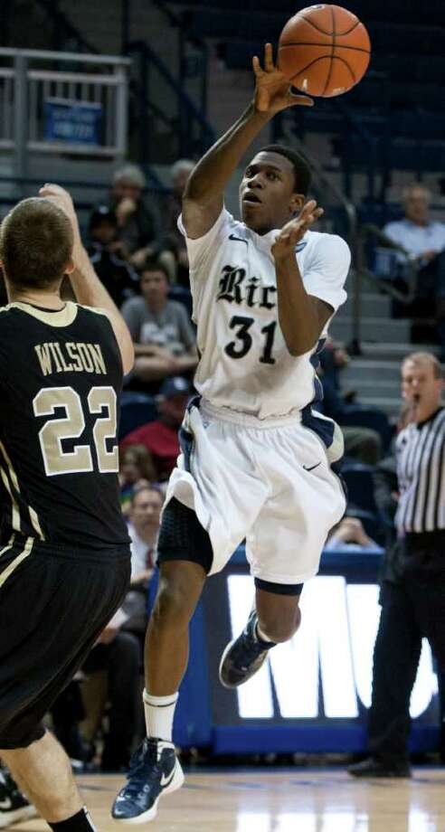 Rice Owls guard Dylan Ennis, right, passes off the ball during the second half of the NCAA basketball game between the Rice Owls and the UCF Knights at Tudor Fieldhouse on Wednesday, Feb. 22, 2012, in Houston.  Rice defeated UCF 83-74 as Owls head coach Ben Braun recorded his 600th career win. Photo: Andrew Richardson, Houston Chronicle / © 2012 Andrew Richardson
