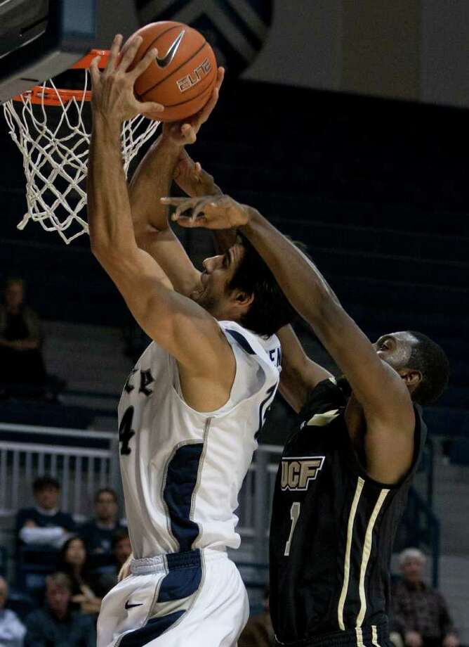 Rice Owls forward Arsalan Kazemi, left, makes a basket during the second half of the NCAA basketball game between the Rice Owls and the UCF Knights at Tudor Fieldhouse on Wednesday, Feb. 22, 2012, in Houston.  Rice defeated UCF 83-74 as Owls head coach Ben Braun recorded his 600th career win. Photo: Andrew Richardson, Houston Chronicle / © 2012 Andrew Richardson