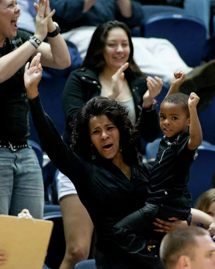 Rice fans Barbara Gill and her son Jayden cheer following an Owls basket during the second half of the NCAA basketball game between the Rice Owls and the UCF Knights at Tudor Fieldhouse on Wednesday, Feb. 22, 2012, in Houston.  Rice defeated UCF 83-74 as Owls head coach Ben Braun recorded his 600th career win. Photo: Andrew Richardson, Houston Chronicle / © 2012 Andrew Richardson