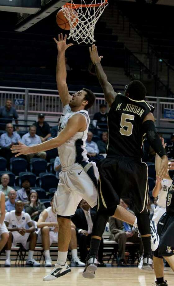 Rice Owls forward Ahmad Ibrahim, left, makes a layup during the second half of the NCAA basketball game between the Rice Owls and the UCF Knights at Tudor Fieldhouse on Wednesday, Feb. 22, 2012, in Houston.  Rice defeated UCF 83-74 as Owls head coach Ben Braun recorded his 600th career win. Photo: Andrew Richardson, Houston Chronicle / © 2012 Andrew Richardson