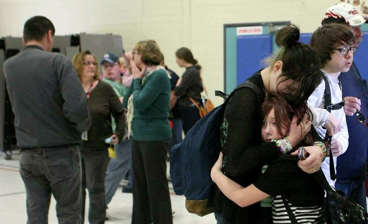 Savannah Anderson, 13, hugs her little sister Kaylee, 10, after arriving to the gymnasium of Armin Jahr Elementary School to take her home after a shooting at the school in Bremerton, Wash. on Wednesday, Feb. 22, 2012. An 8-year-old girl was shot in the abdomen and one of her classmates was detained, authorities said.