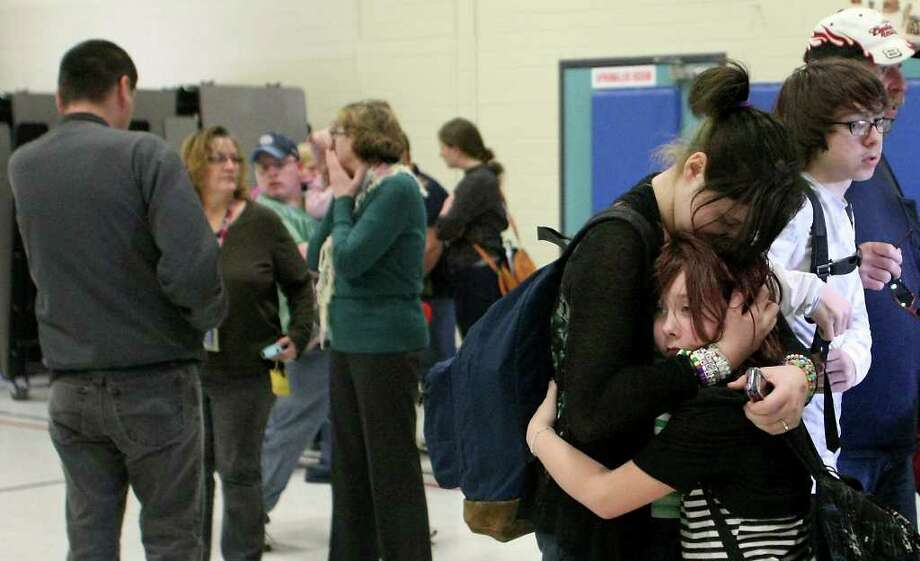 Savannah Anderson, 13, hugs her little sister Kaylee, 10, after arriving to the gymnasium of Armin Jahr Elementary School to take her home after a shooting at the school in Bremerton, Wash. on Wednesday, Feb. 22, 2012. An 8-year-old girl was shot in the abdomen and one of her classmates was detained, authorities said. Photo: Kitsap Sun, Meegan M. Reid
