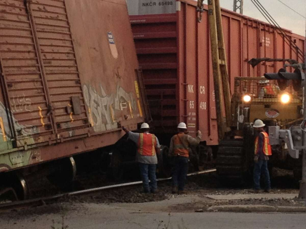 Workers inspect derailment to untangle the rail cars at West Hollywood and North Flores.