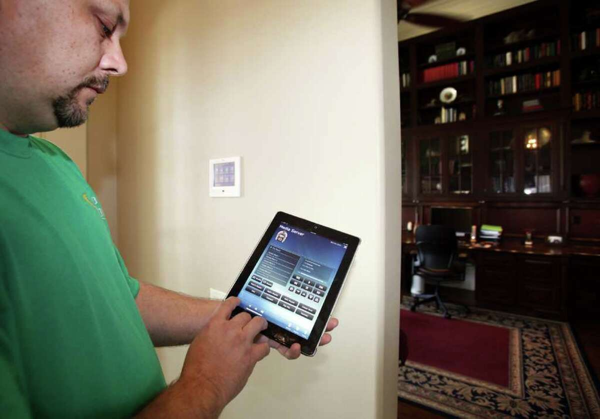 Chip Snyder, owner of Good Vibrations Custom Home Theater shows how an ipad can be used to control the electronic home system, in the home of Dan Bagwell. Tuesday, Feb. 21, 2012. Bob Owen/Express-News