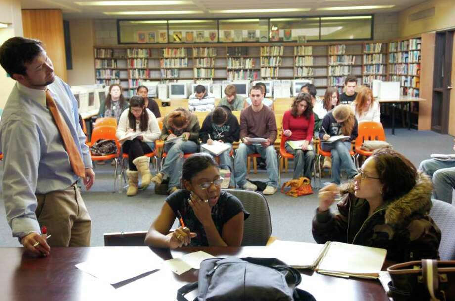 In this file photo, students in Norwalk High School's journalism class discuss story ideas with teacher Rob Karl. Photo: ANDREW SULLIVAN, ST / 00001738A