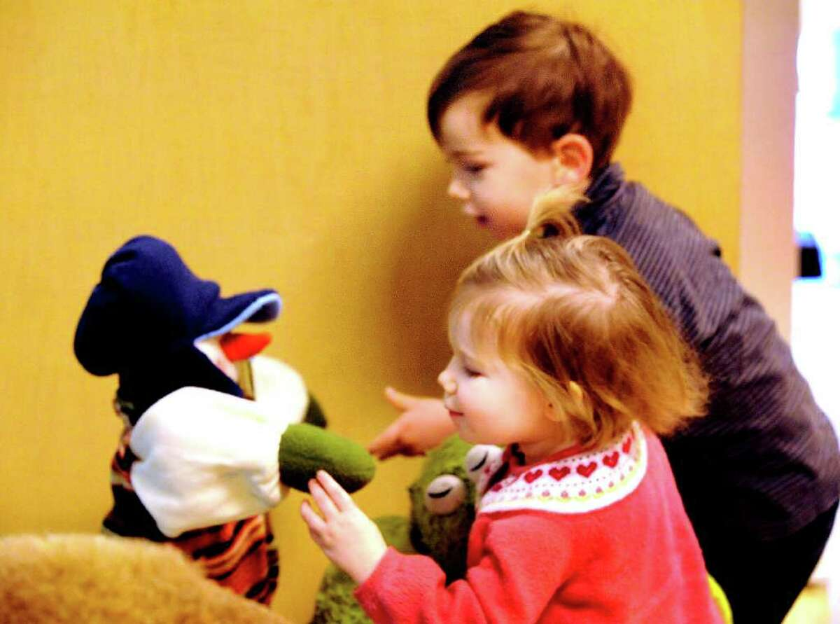 Kate McGuire, 1, and her brother, James, 3, greet a snowboy on display in the children's section of the Danbury Public Library Thursday, Feb. 23, 2012.
