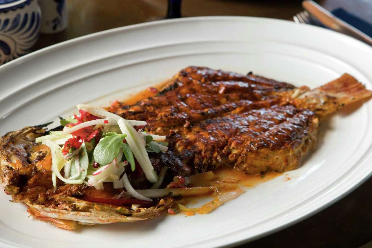 A plate of Pescado Zarandeado, a grilled red snapper, butterflied and rubbed with achiote and served with a jicama salad, at Hugo's