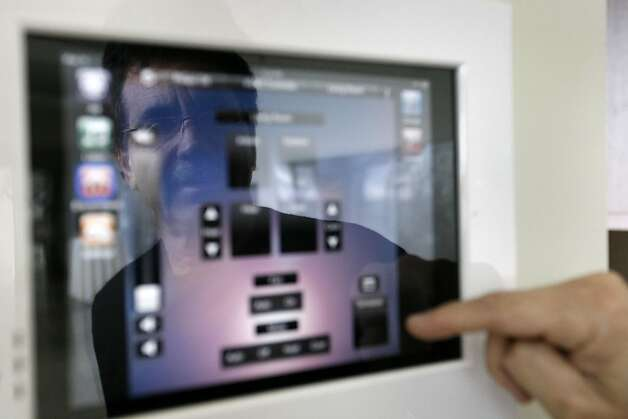 Jeff Paster, owner of the Villa Belvedere, uses one of the six iPads located in the house. Villa Belvedere is a smart house located in Belvedere looking over the Richardson Bay and on to San Francisco. Photo: Sean Culligan, The Chronicle