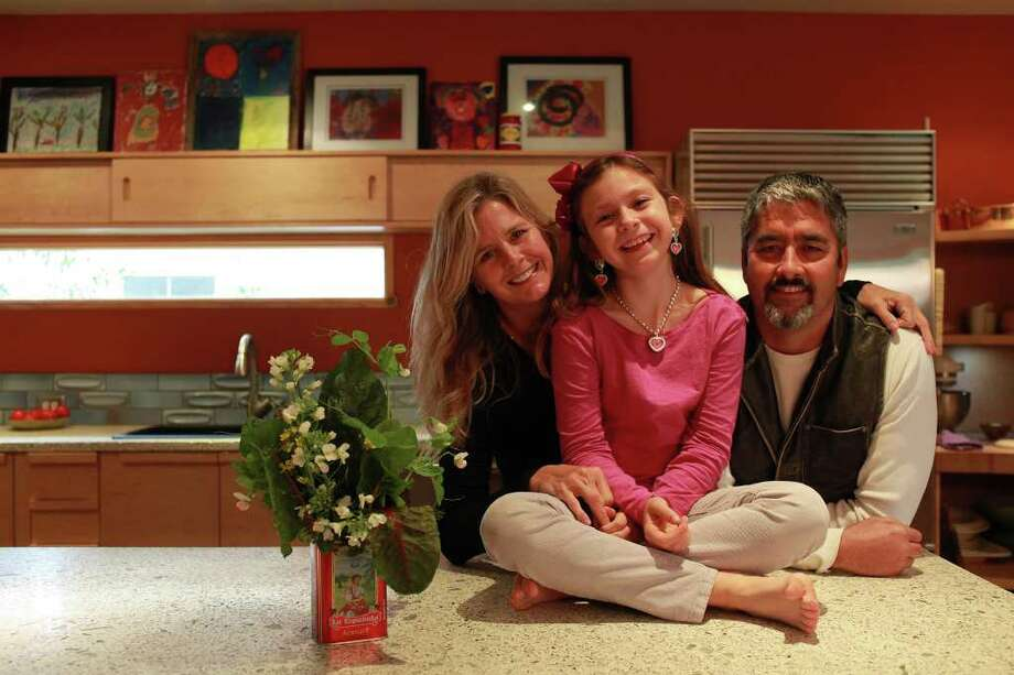 Karla Toye and Lydell Toye stand with their daughter, Ella Toye, 8, in the kitchen of their Alamo Heights home on Saturday, Feb. 4, 2012. Photo: Lisa Krantz, San Antonio Express-News / @2012 SAN ANTONIO EXPRESS-NEWS