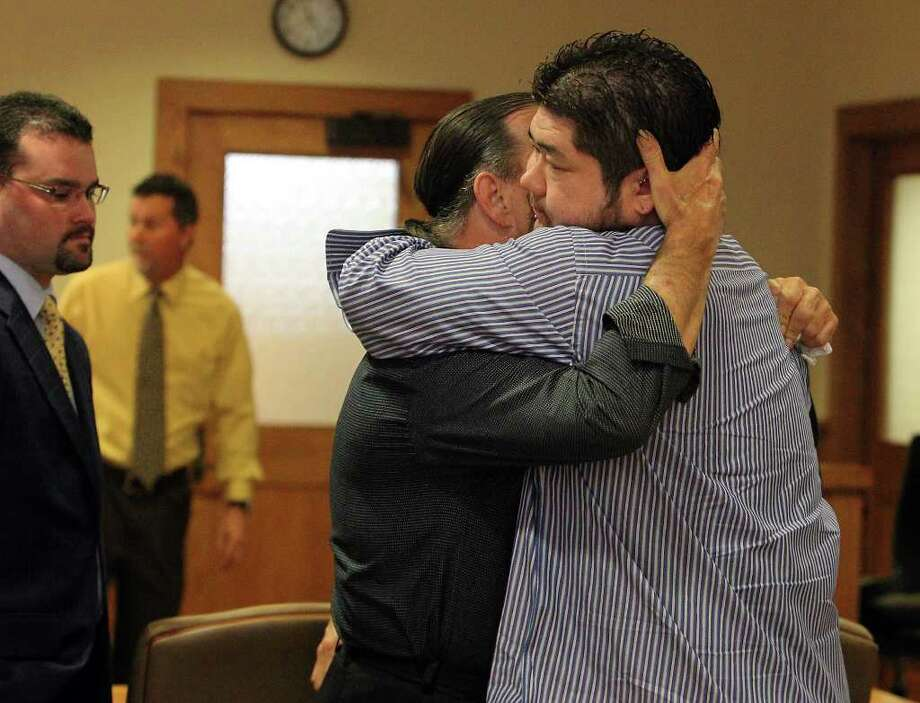 Noah Yuchnitz (right) hugs his dad, Mike Yuchnitz, at the conclusion of the father's divorce trial with Tina Yuchnitz. Photo: Kin Man Hui, San Antonio Express-News / San Antonio Express-News
