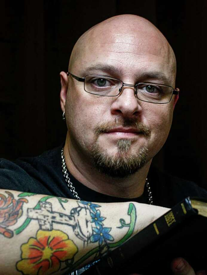 Scott Hill poses for a photo inside his tattoo studio Anointed Ink, which is marketed as a Christian business without rap music, nudity or lewd messages, Tuesday, Jan. 17, 2012, in Huffman.  Hill, also a praise and worship leader at his church, operates the studio out of his own faith and as a family-friendly places to get ink.  ( Michael Paulsen / Houston Chronicle ) Photo: Michael Paulsen / © 2011 Houston Chronicle