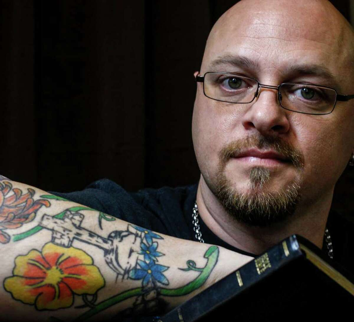 Scott Hill poses for a photo inside his tattoo studio Anointed Ink, which is marketed as a Christian business without rap music, nudity or lewd messages, Tuesday, Jan. 17, 2012, in Huffman. Hill, also a praise and worship leader at his church, operates the studio out of his own faith and as a family-friendly places to get ink. ( Michael Paulsen / Houston Chronicle )