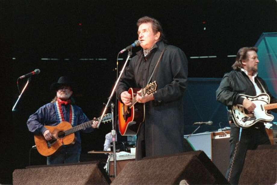 Johnny Cash, center, Willie Nelson, left, and Waylon Jennings of The Highwaymen perform during the 1990 Houston Livestock Show and Rodeo.