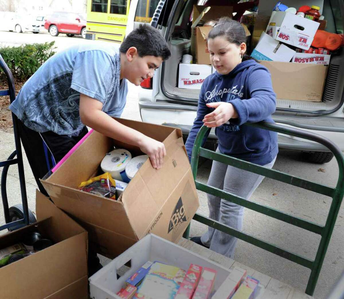 """Jarod Rodriguez, left, and Tais Nunez, both 10, help load a van with items to be donated to the Dorothy Day Hospitality House in Danbury. Shelter Rock School organized a a project called, """"Hearts United Against Hunger,"""" as a way of recognizing its 100th day of school by giving back to the community. Photo taken Wednesday, Feb. 22, 2012."""
