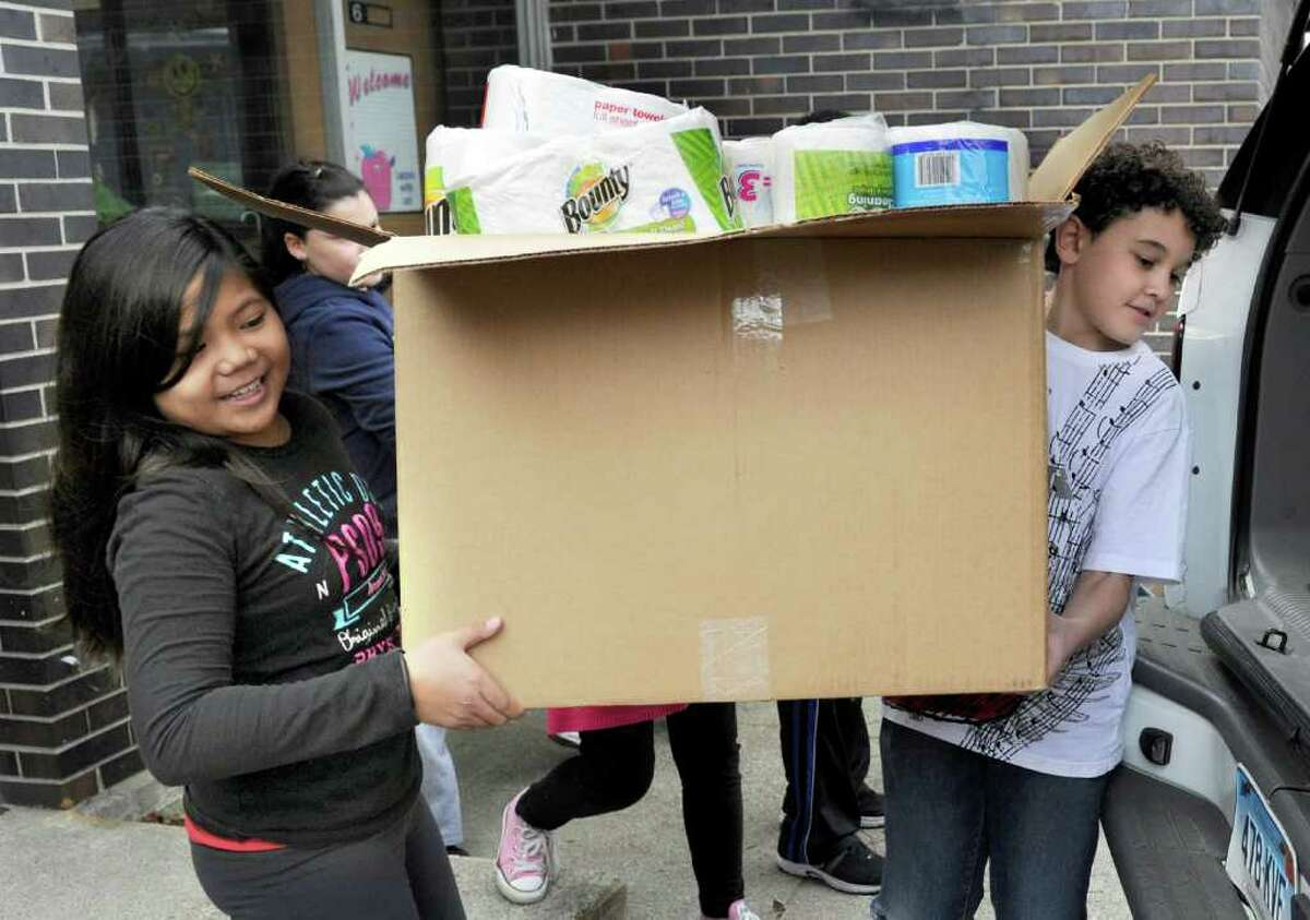 """Jaymeejoy Alfonso, left, and Julian Weed, fifth-graders in teacher Ida Lucarelli's class, help load a van with items to be donated to the Dorothy Day Hospitality House in Danbury. Shelter Rock School organized a project called, """"Hearts United Against Hunger,"""" as a way of recognizing its 100th day of school by giving back to the community."""
