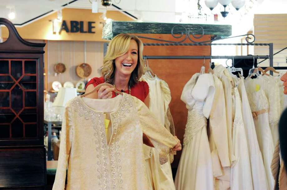 "Greenwich resident Lara Spencer, the lifestyle anchor for ""Good Morning America,""  looks at wedding gowns at the Greenwich Hospital Auxiliary Thrift Shop Thursday, Feb. 23, 2012 for a segment for a featuring on thrift stores. The shop is showcasing its selection of designer wedding gowns and tuxedos. Photo: Helen Neafsey / Greenwich Time"