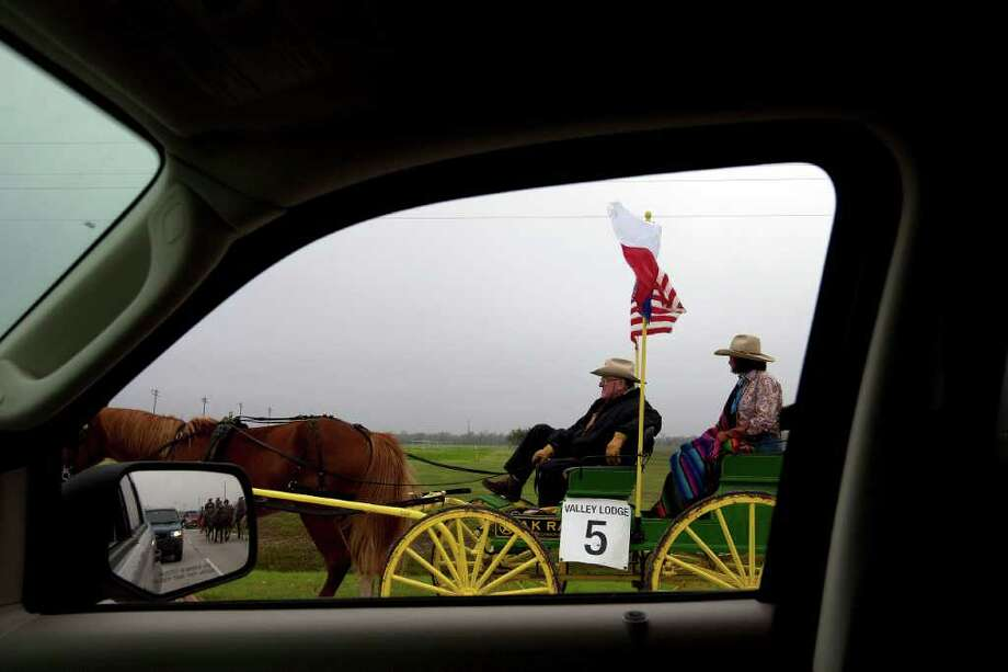 A confident Valley Lodge trail rider is seen through a car window as he and the riding groups other riders make their 71 mile journey from Brookshire to Houston on horseback or wagon. Photo: Johnny Hanson, Houston Chronicle / © 2012  Houston Chronicle