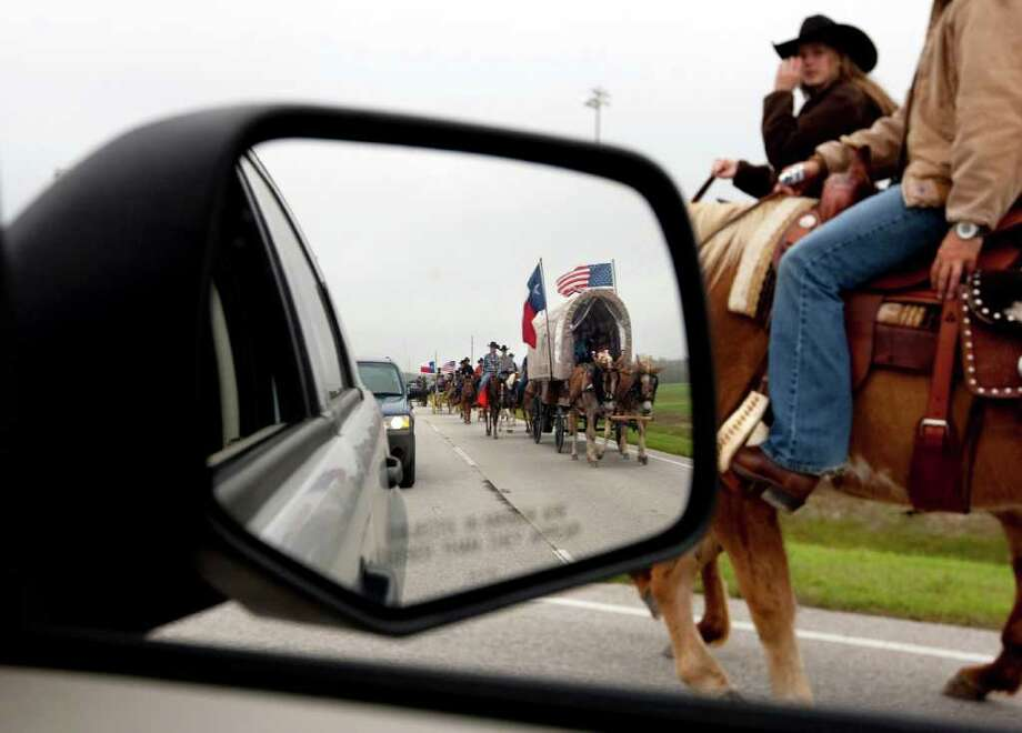 Valley Lodge trail riding group's horse back riders lead the groups caravan of wagons through George Bush Park in Houston. The trail riding group, established in 1959, has more than 100 riders on the trail ride. Photo: Johnny Hanson, Houston Chronicle / © 2012  Houston Chronicle