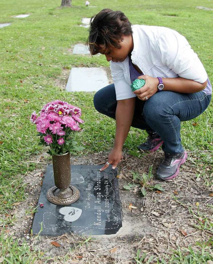 Kenya Stradford caresses the headstone of daughter Kendyll Anya Stradford at Forest Park Cemetery on Thursday, Feb. 23, 2012, in Houston. Kenya Stradford will observe the anniversary of her daughter's death in the daycare fire, which happened last year on Feb. 24, 2011. Photo: Mayra Beltran, Houston Chronicle / © 2012 Houston Chronicle