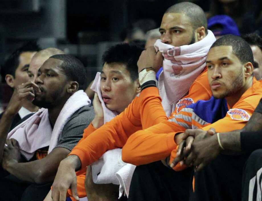 New York Knicks players, from right, Iman Shumpert, Tyson Chandler and Jeremy Lin react while watching game action during the second half of an NBA basketball game against the Miami Heat on Thursday, Feb. 23, 2012 in Miami. Photo: AP