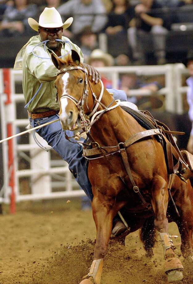 Tie-down roper Fred Whitfield dismounts during his 10.3 ride and rope at the San Antonio Stock Show and Rodeo on Thursday, Feb. 23, 2012. Billy Calzada / San Antonio Express-News Photo: Billy Calzada, San Antonio Express-News / San Antonio Express-News