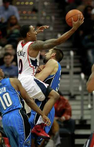 Atlanta point guard Jeff Teague (0) is fouled by Orlando power forward Ryan Anderson (33) while driving to the basket in the second half of an NBA basketball game on Thursday, Feb. 23, 2012, in Atlanta. Atlanta won 83-78. Photo: AP
