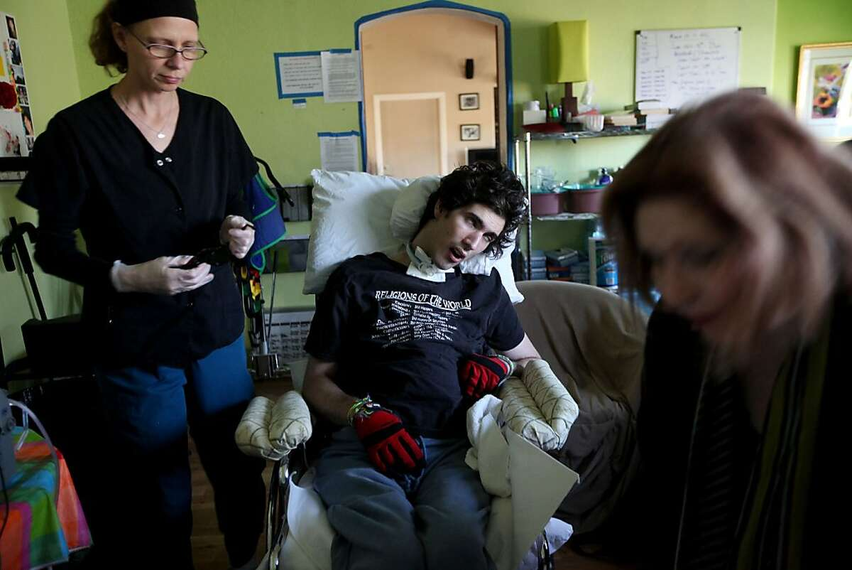 Madelyn Bennett,R, and aide Teresa Beatty secure John Gibson in a wheelchair before taking him on a walk at their home in San Diego on Friday March 11, 2011. Gibson suffered a heart attack while at UC Berkeley after ingesting illicit drugs and is now in a minimally conscious state.
