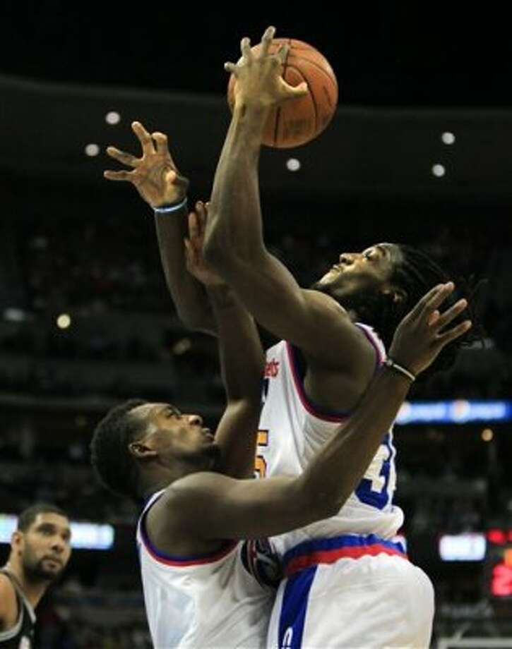 Denver Nuggets' Jordan Hamilton, front left, and Kenneth Faried, right, collide in midair while reaching for a rebound against the San Antonio Spurs during the second quarter of an NBA basketball game on Thursday, Feb. 23, 2012, in Denver. (AP Photo/Barry Gutierrez) (AP)