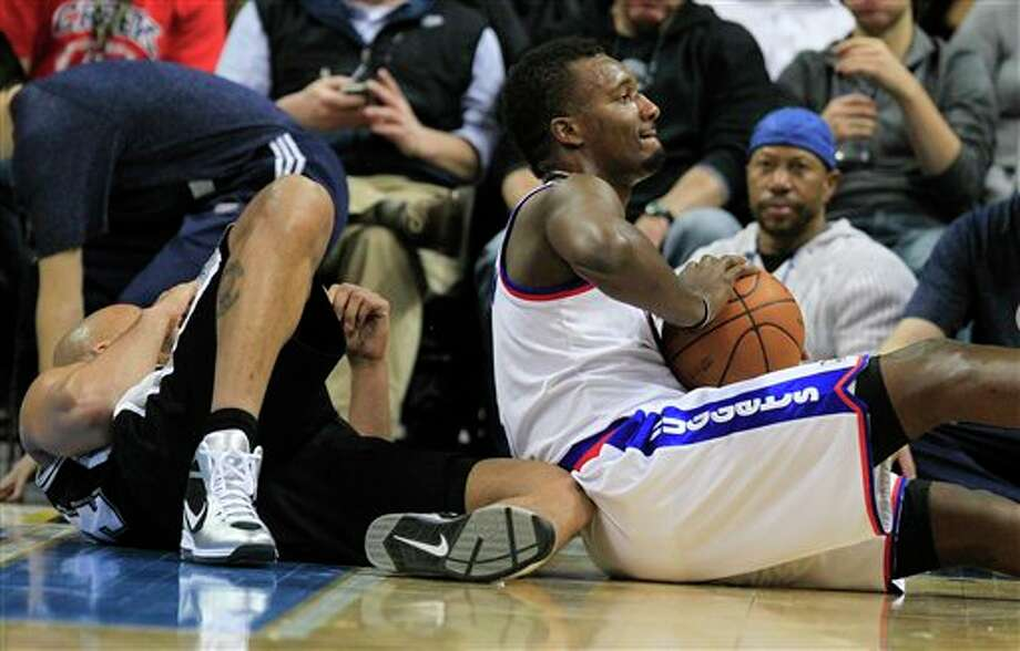 Denver Nuggets guard Jordan Hamilton, from right, holds onto the ball after colliding with San Antonio Spurs small forward Richard Jefferson during the first quarter of an NBA basketball game on Thursday, Feb. 23, 2012, in Denver. (AP Photo/Barry Gutierrez) (AP)